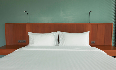 white pillows in empty white bed in hotel room Stock Photo