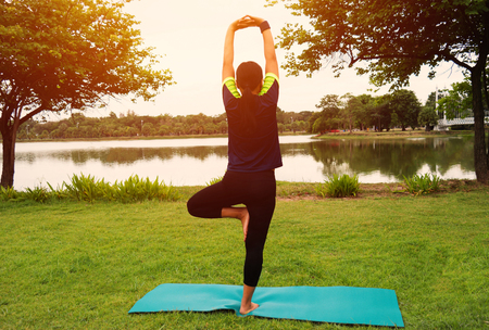 young asian woman standing for yoga pose in park Stock Photo