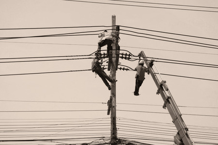 men hanging and working on electrical pole Stock Photo