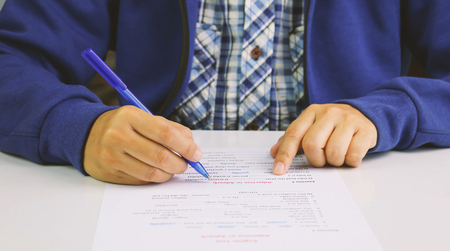 hand holding blue pen taking English test on table Stock Photo