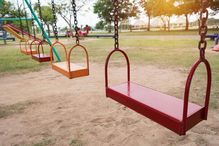 empty colorful swing set in playground in park Stock Photo