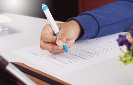 students hand holding blue pen taking English test on white desk in class