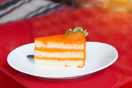 slice of orange cake on white plate in coffee shop