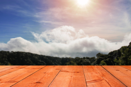 brown wooden board over blur green mountain and blue sky in summer