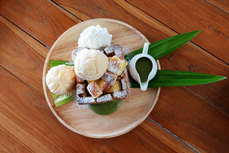 top view pandan custard honey toast on wooden plate on table 写真素材