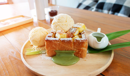 honey toast with pandan custard on wooden plate on table in coffee shop