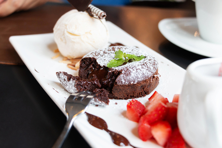 well decorated chocolate lava cake with ice cream and strawberry on white plate
