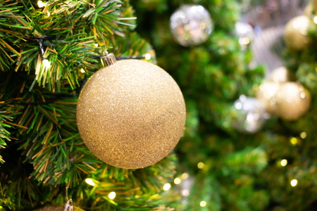 golden ball decorated on christmas tree with blur background