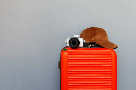 orange baggage with camera and cap in front of gray wall for background