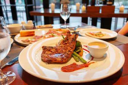 juicy grilled pork chop on white plate in restaurant for dinner
