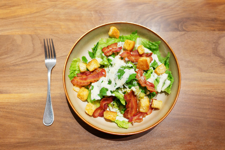 top view of ceasar salad with bacon and bread on wooden table