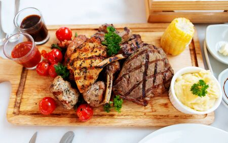 top view of mixed meat steak on wooden plate in restaurant