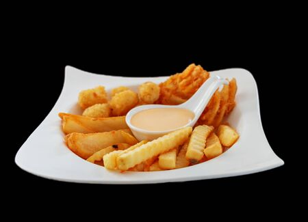 isolated white plate of mixed fries with dipping