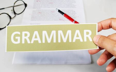 grammar word card over blur paper on white table represent proofreading based on grammar
