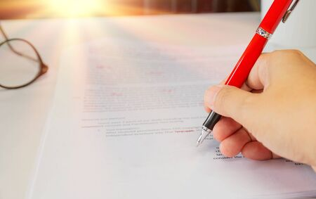 proofreading paper on white table with hand and red pen
