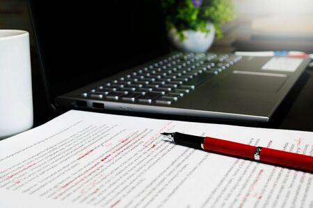 Korrekturleseblatt auf Tisch mit rotem Stift und Laptop verwischen Standard-Bild