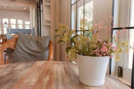 wooden table with flowers and copy space by window in coffeehouse 写真素材
