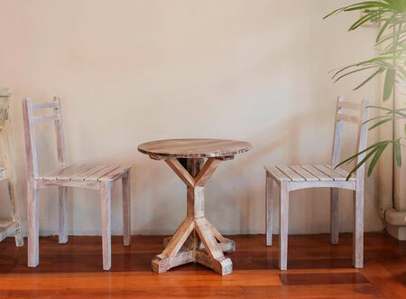 retro wooden table set with two chairs over empty white wall for copy space