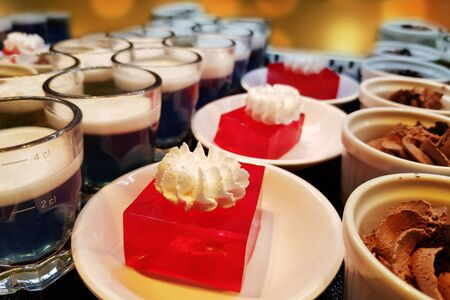 red jelly with cream on top on white dish in restaurant