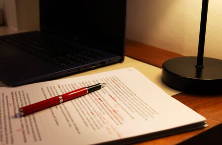 blur proofreading paper and computer laptop on table under lamp light 版權商用圖片