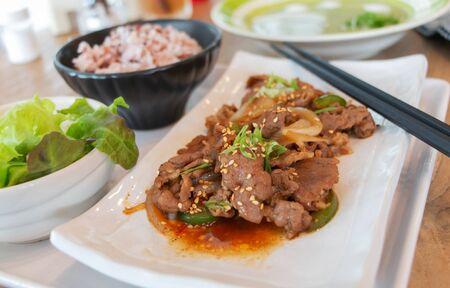 stir fried korean pork dish in white plate on table