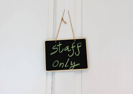 small blackboard hanging on door for staff only