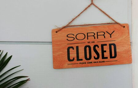 brown wooden signboard hanging on wall in front of shop