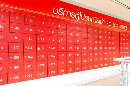 row of red mailbox with white number for service