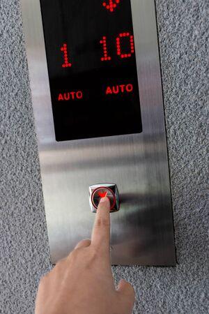 finger pressing on elevator button for service
