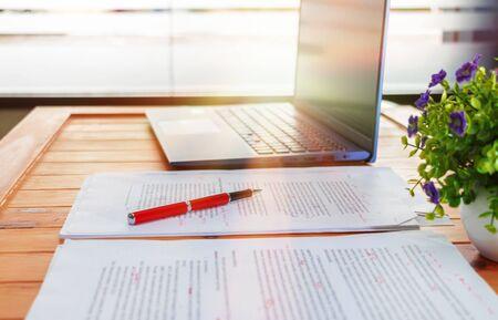 Konzept des Korrekturlesens mit Stift, unscharfem Text und Laptop auf dem Schreibtisch im Büro