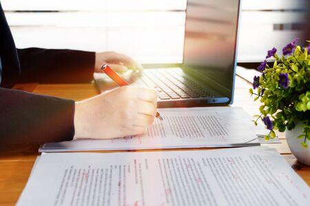 Hand, die an der Bearbeitung von Unschärfetext auf dem Schreibtisch mit Laptop im Büro arbeitet