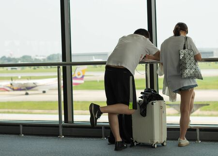 Bangkok, THAILAND- 2 October,2019: two young asian adults waiting for airplane flight to travel Banco de Imagens