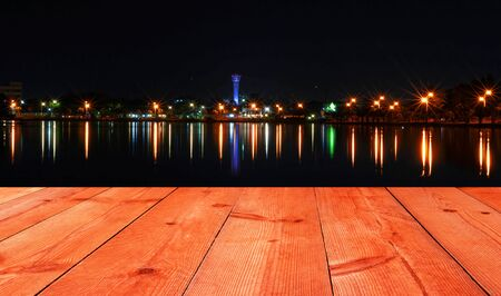 perspective wooden board over cityscape light and reflection in lake at night
