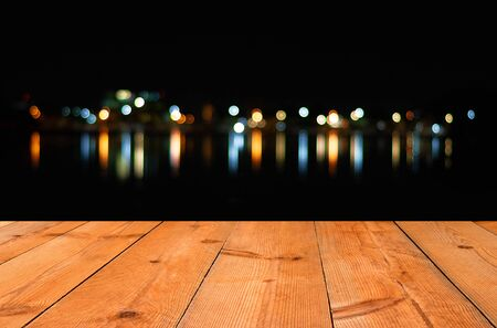 perspective wooden board over blur bokeh dot light and reflection in dark