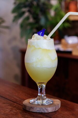 cold yellow pineapple juice in glass on wooden table in restaurant