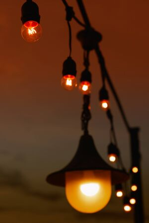 electric light bulb hanging on wire for decoration at night