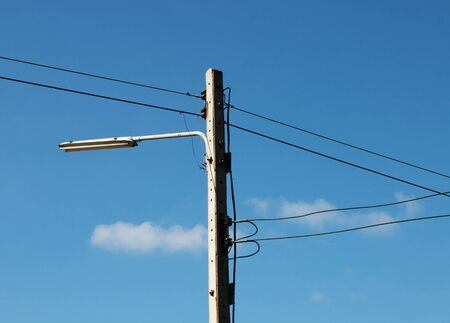 isolated electric pole with wire and light bulb over blue sky