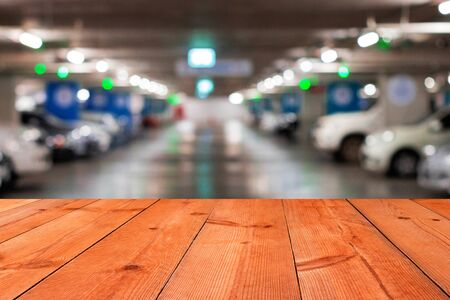 perspective of brown wooden board over blurred underground parking lot in building