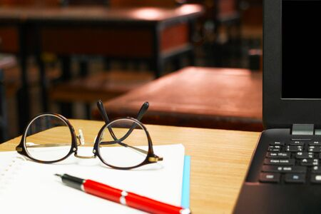 glasses, pen, and computer on teachers table in classroom