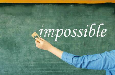 hand erasing prefix of impossible on chalkboard in classroom