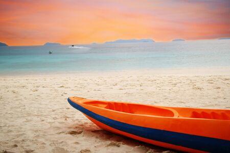 orange kayak boat on beach by blue sea under orange sky Banco de Imagens
