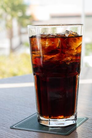 glass of cold soft drink on wooden bar with blurred summer view