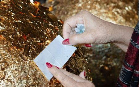 hand of buddhist gilding gold leaflet on golden ball in temple to worship buddha