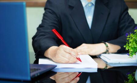 hand holding red pen to proofread on black table in office