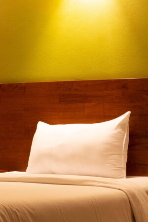single white pillow in bed under lamp light Stock Photo