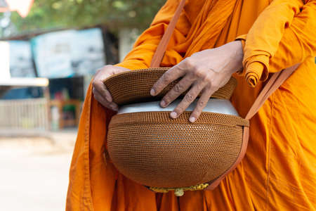 close up buddhist monk hand holding alms bowl to alms round in the morning