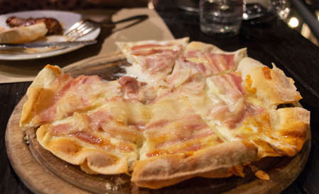 fresh juicy baked bacon pizza on wooden plate on table in restaurant at night