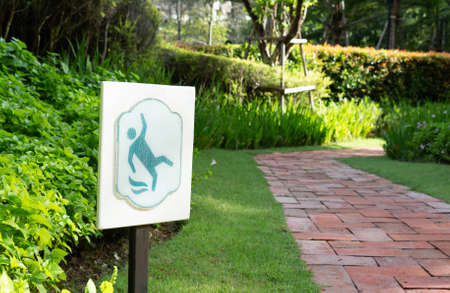 slippery sign beside walkway in garden in morning to warn for caution