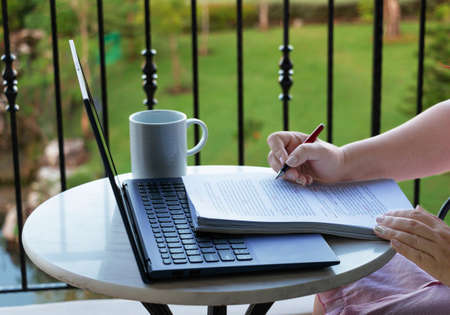 hand holding pen over paperwork with laptop on balcony represents work from home