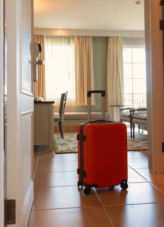 orange brand new luggage arrive in luxury hotel room for trip